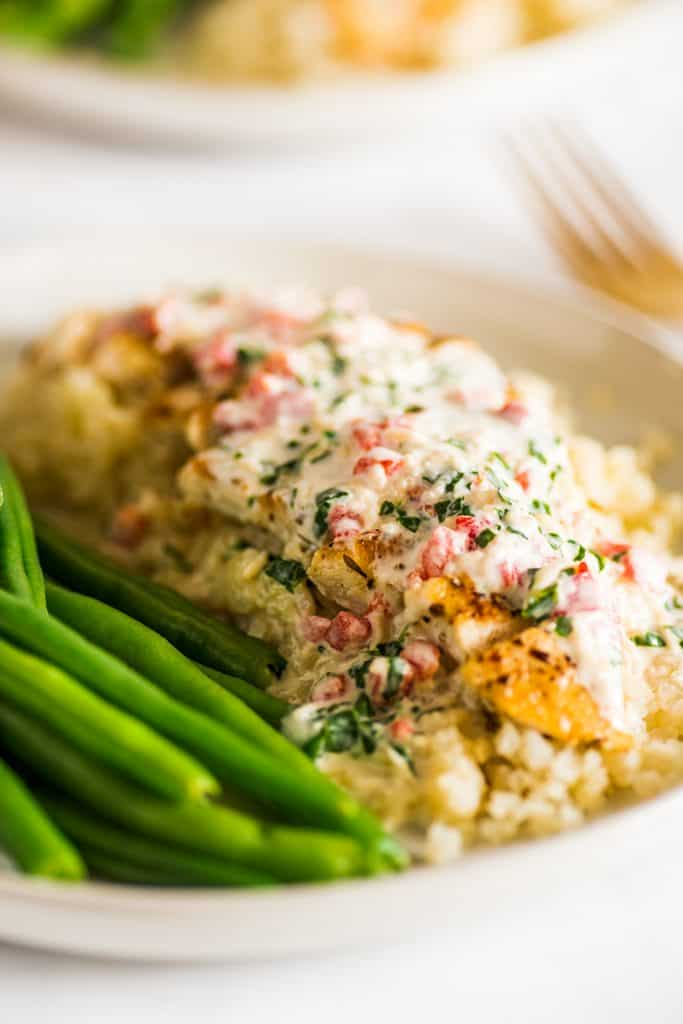 Close up image of keto chicken over cauliflower rice with cream sauce on a plate with green beans.