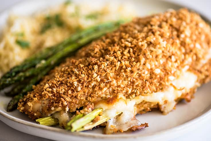 Image of asparagus-stuffed chicken breast on a white plate with orzo and roasted asparagus.