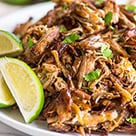 Easy Carnitas Recipe on a white plate with limes.