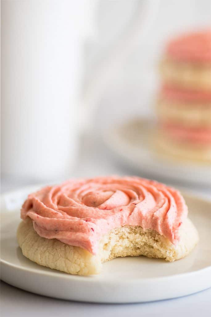 Picture of Lemon Cookies With Strawberry Frosting with a bite out of it on a white plate.