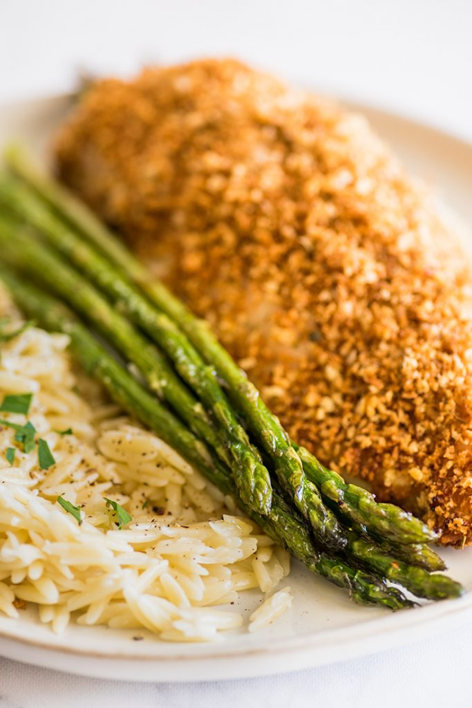Photo of roasted asparagus on a plate with chicken and orzo.