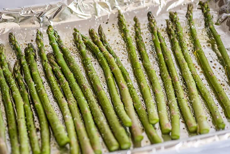 Asparagus in the oven step 2 photo of asparagus on a baking sheet about to be roasted.