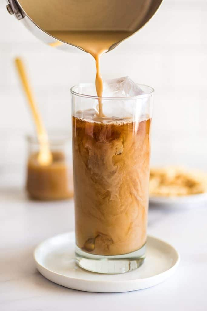 Iced Caramel Macchiato being poured over ice.