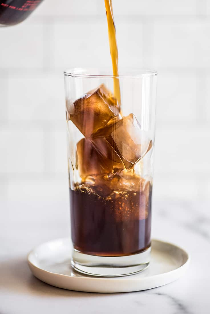 Coffee being poured over coffee ice cubes.