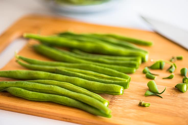 Green beans on a cutting board with ends trimmed.