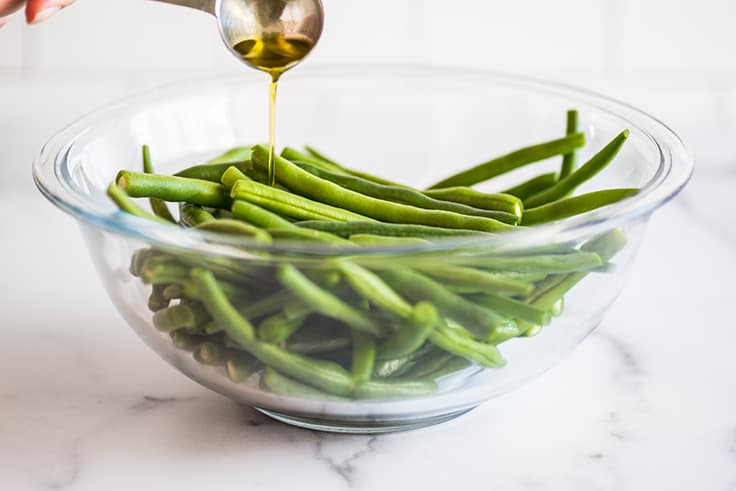 Green beans in a bowl being drizzled with olive oil.