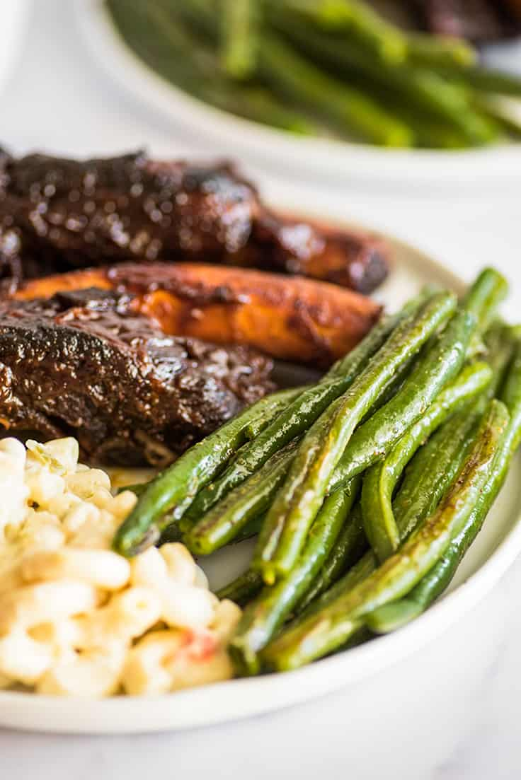 Roasted green beans on a plate with ribs.