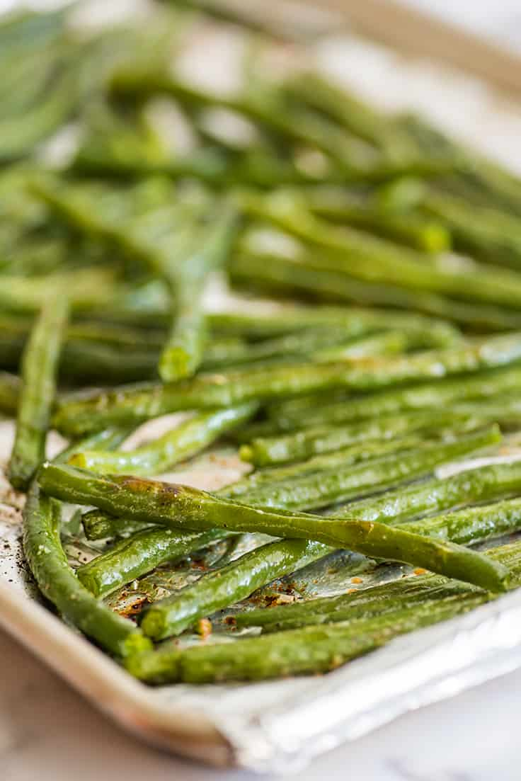 Roasted green beans on a baking sheet.