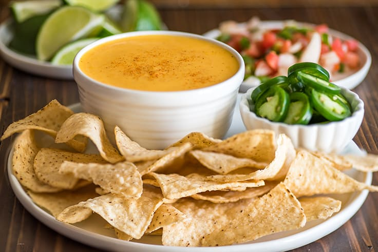 Image of nacho cheese in a white bowl with tortilla chips.