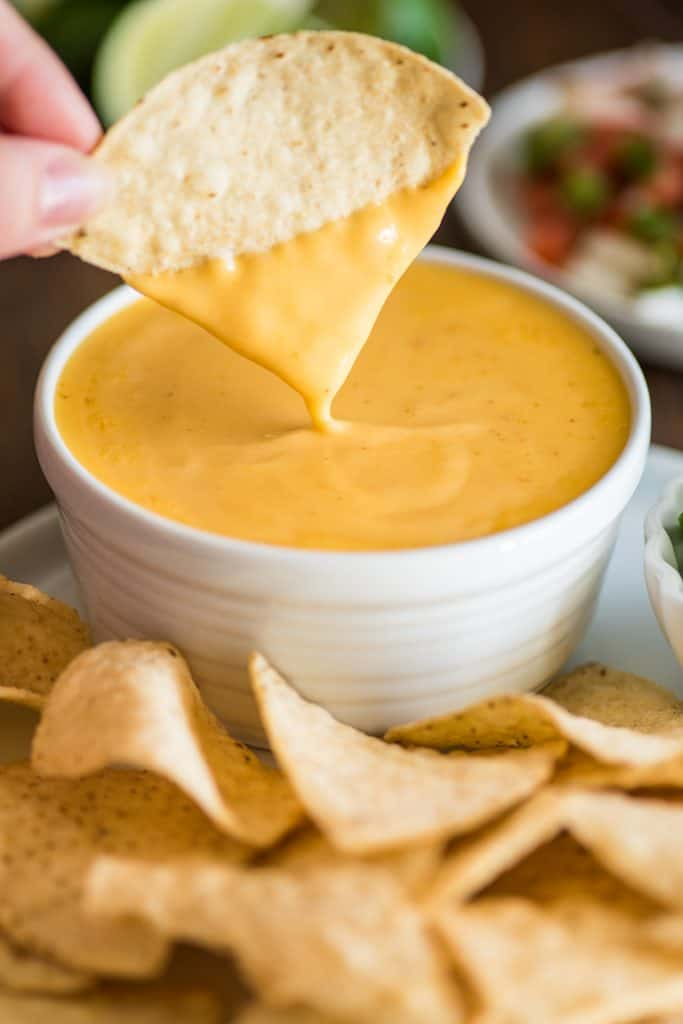 Picture of tortilla chip being dipped into homemade nacho cheese.