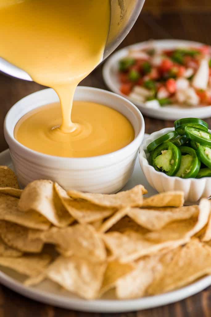 Photo of nacho cheese being poured into a white bowl next to tortilla chips.