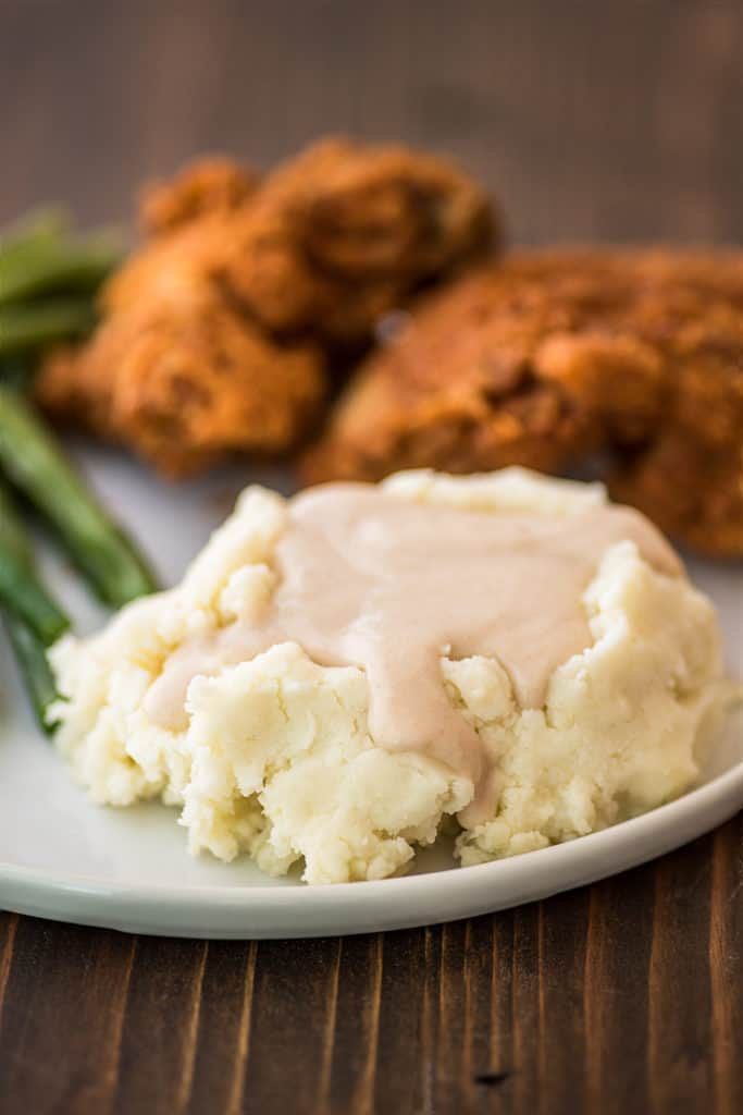 Easy gravy over mashed potatoes on a plate.