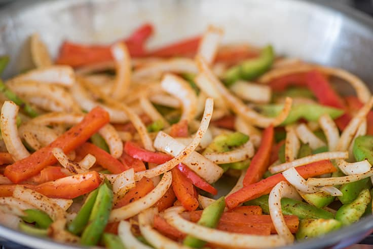 Onions and red and green bell peppers in a skillet for fajitas.