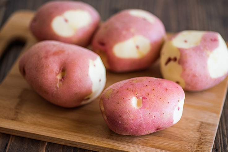 Red potatoes on a cutting board.