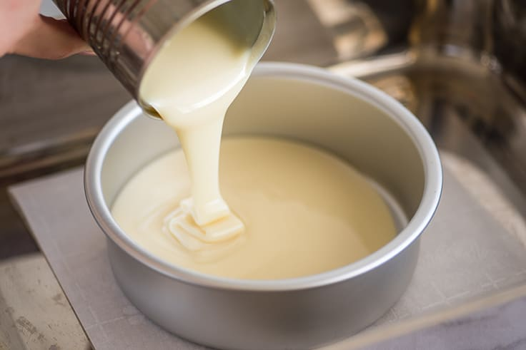 Picture of condensed milk being poured into a cake pan for dulce de leche.