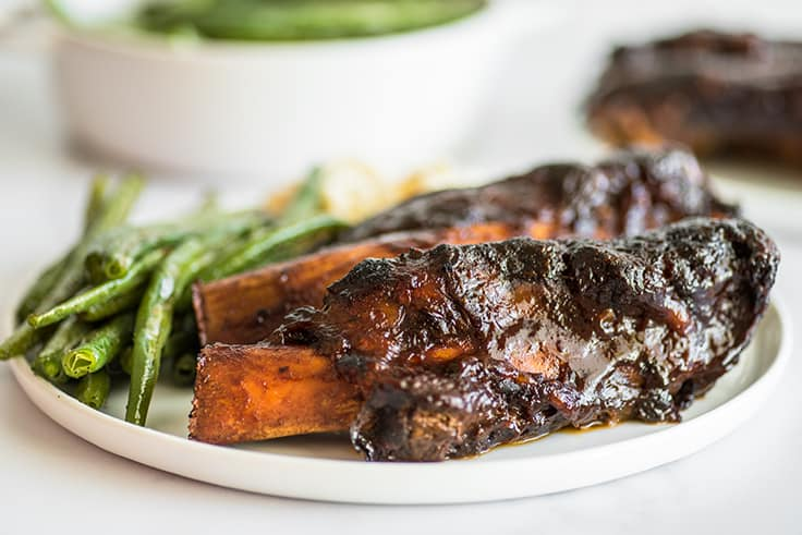 Beef ribs on a plate with green beans.