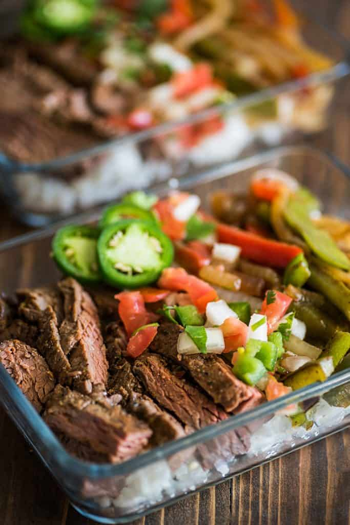 Photo of meal prep steak fajita bowls with rice in glass containers.