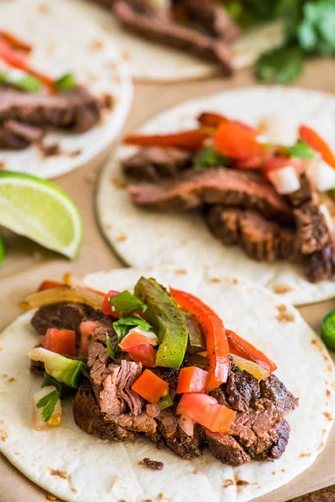 Picture of steak fajitas with carne asada and bell peppers on tortillas.