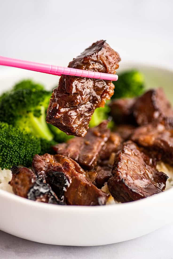 A piece of Beef Teriyaki being held by chopsticks.