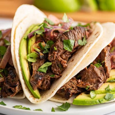 Three carne asada tacos with avocado on a plate.