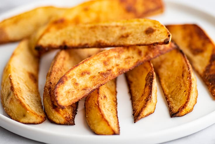 Oven-baked fries on a plate.