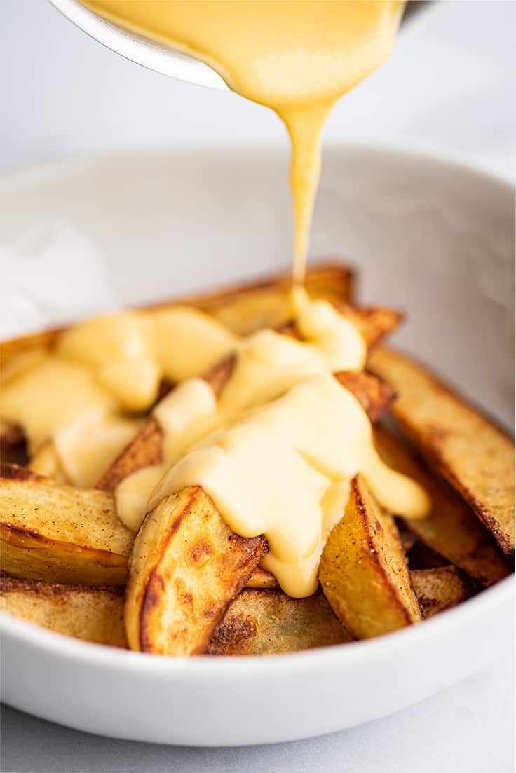 Cheese sauce being poured over fries.