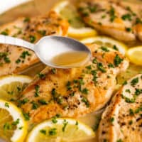 Spooning white wine lemon butter sauce over chicken breast in a skillet.