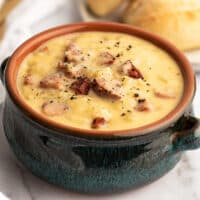 Blue bowl filled with cheesy sausage potato soup.