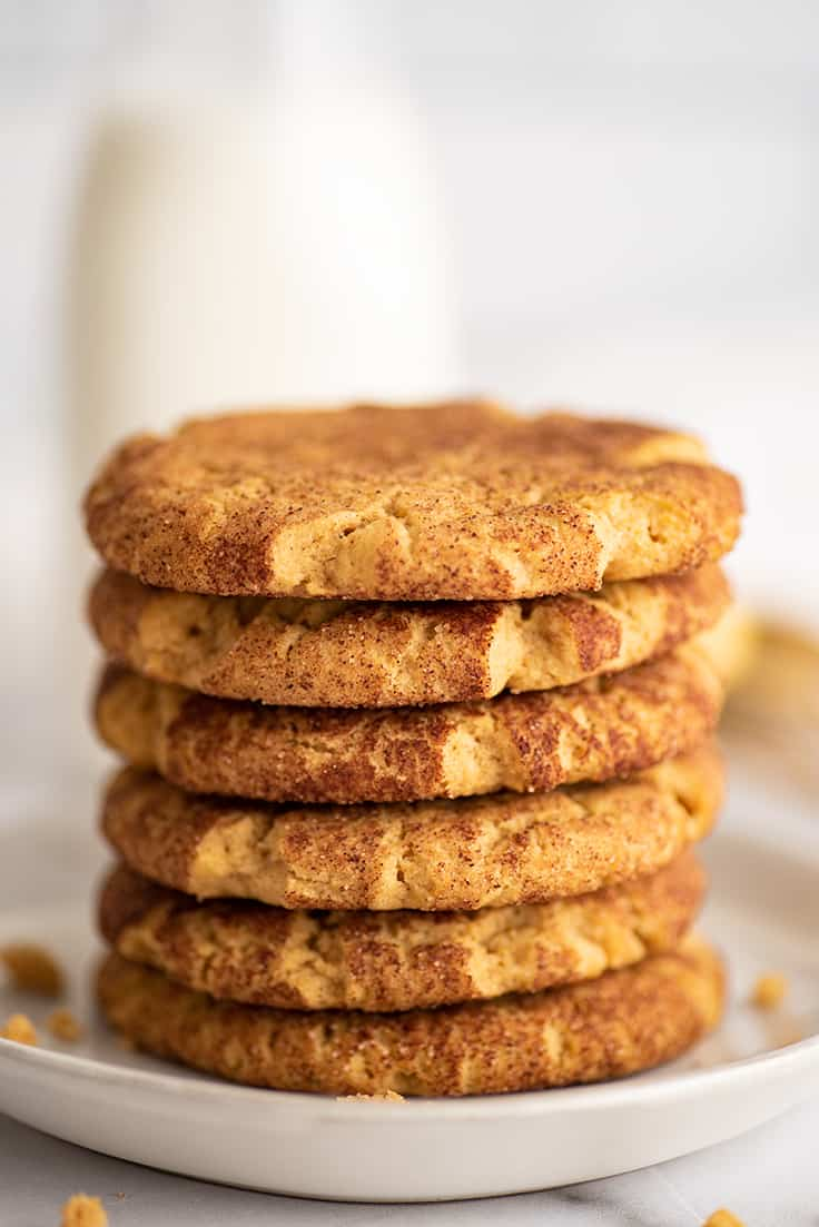 Pumpkin snickerdoodles stacked on a plate.
