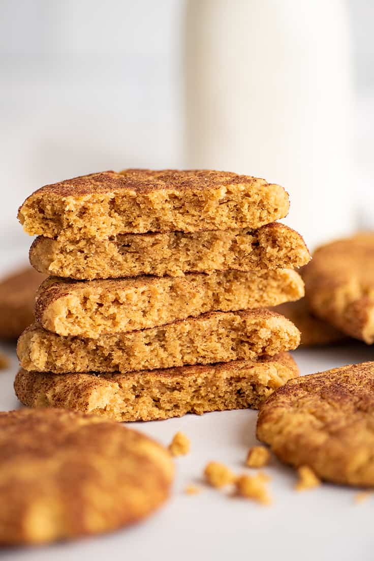 Small batch of pumpkin snickerdoodles stacked by a jar of milk.
