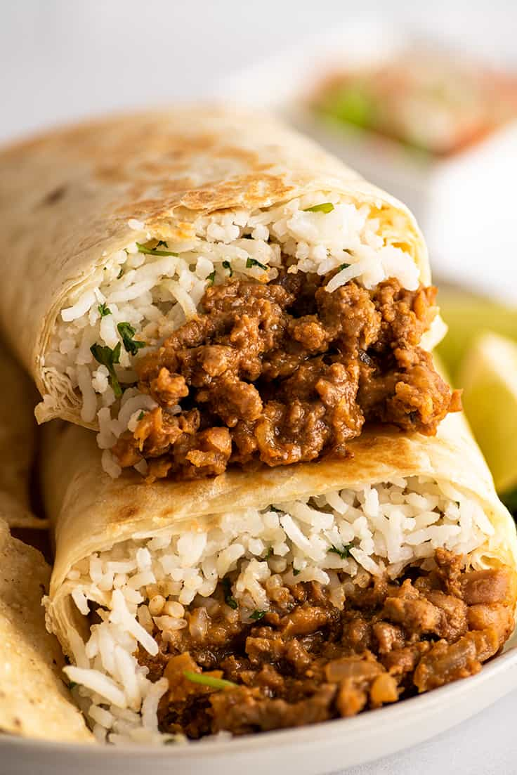 Close up photo of freezer burritos stacked on a plate.