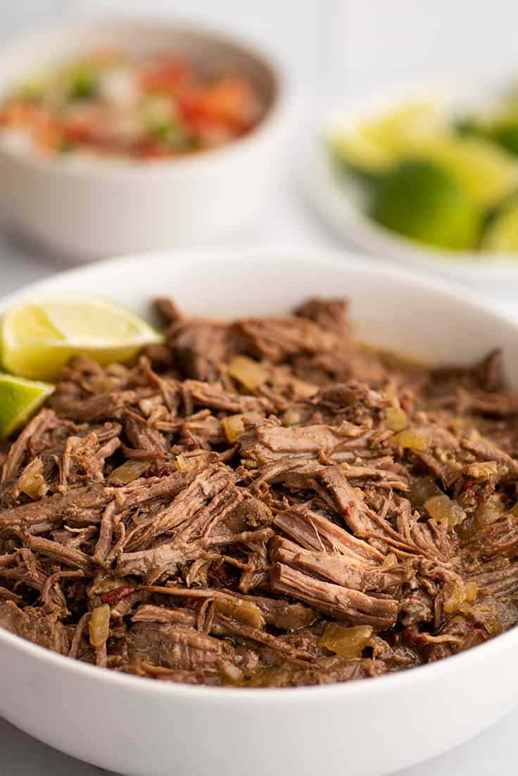 Barbacoa beef in a white bowl.