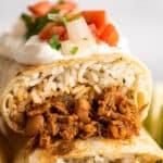 Close up photo of shredded beef burritos stacked.