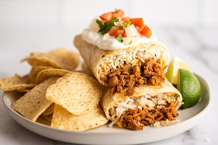 Shredded beef burritos on a white plate with tortilla chips.