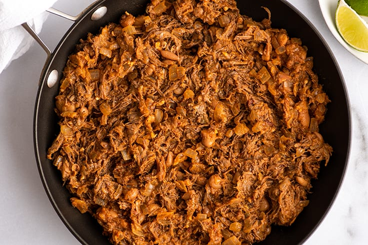 Shredded beef burrito filling in a pan.