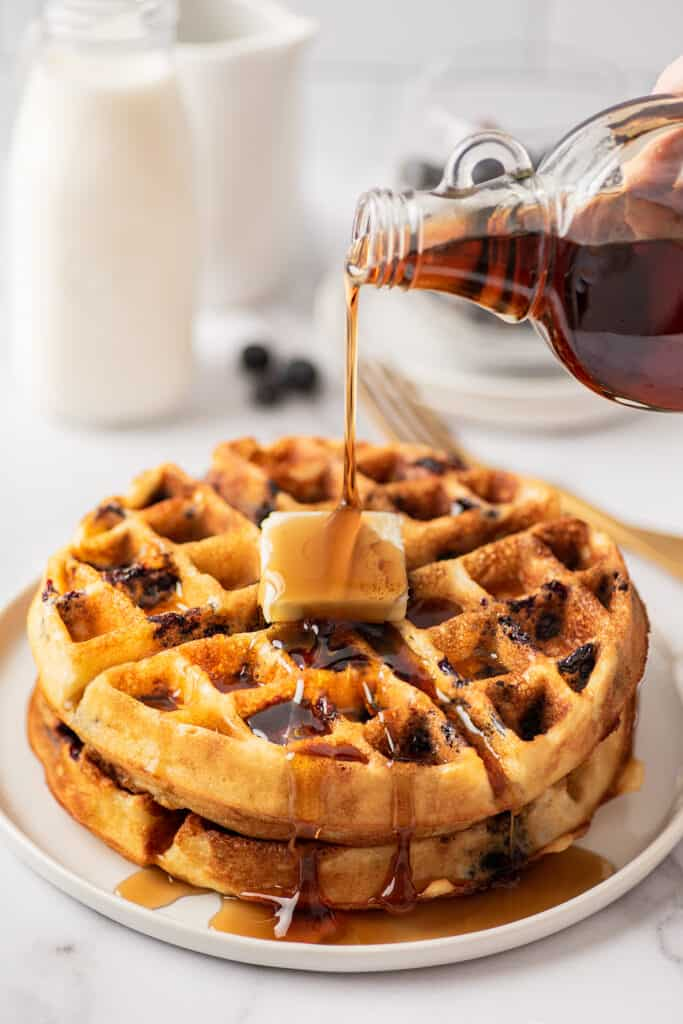 Syrup being poured over blueberry waffles.
