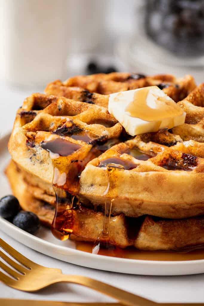 Blueberry waffles stacked on a plate with butter and syrup.