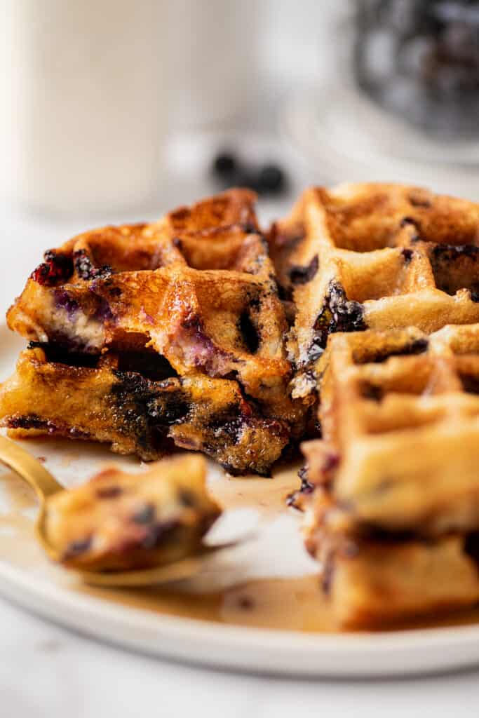 Blueberry waffle pieces on a white plate.