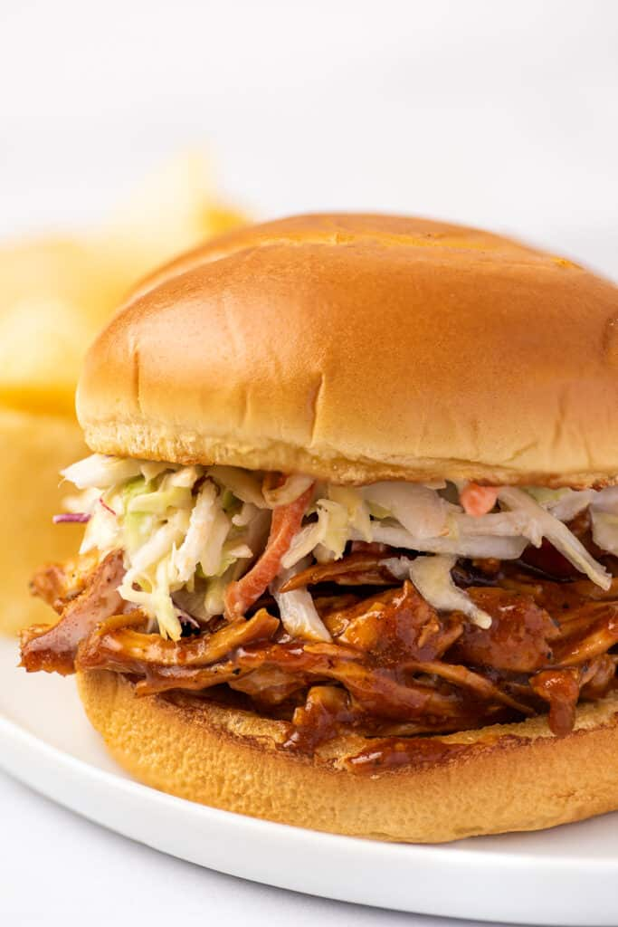BBQ chicken sandwich on a white plate with chip.
