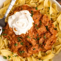 Overhead photo of Hungarian Goulash in a bowl over egg noodles with sour cream.