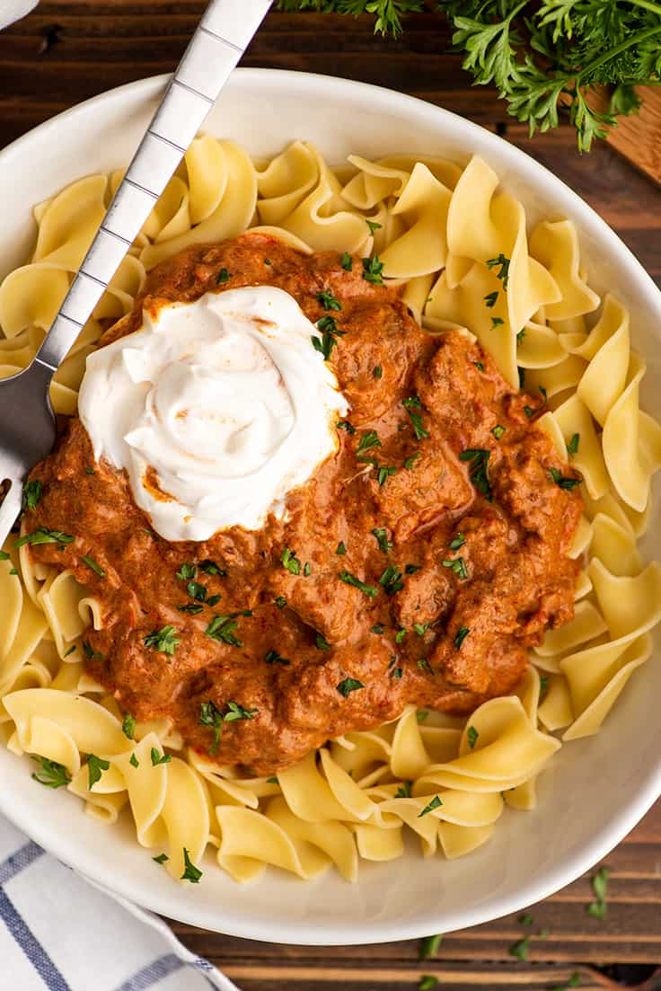 Overhead photo of Hungarian Goulash with noodles with sour cream.
