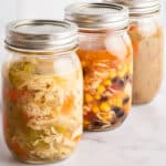 Mason jars of soup ready to be frozen.