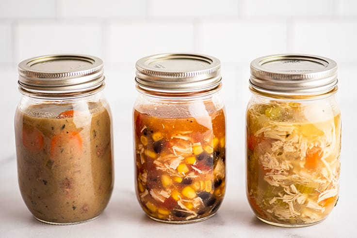 Mason jars of soup on a counter ready to be frozen.