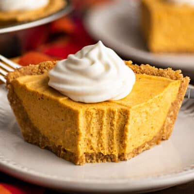 Slice of no-bake pumpkin cheesecake with a bite out of it.