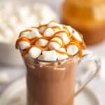 Salted caramel hot chocolate in a mug with marshmallows and caramel drizzle.