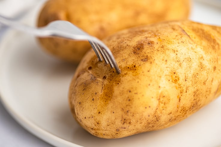 Potato being pierced with a fork before microwaving.