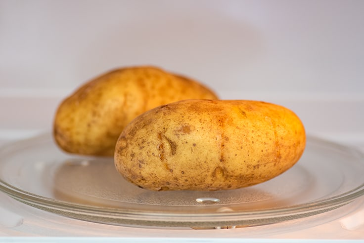 Potato in the microwave for cooking.
