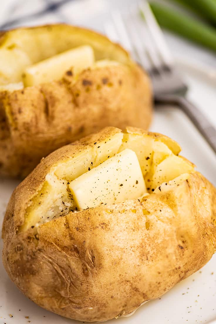 Microwave baked potatoes on a plate with butter.