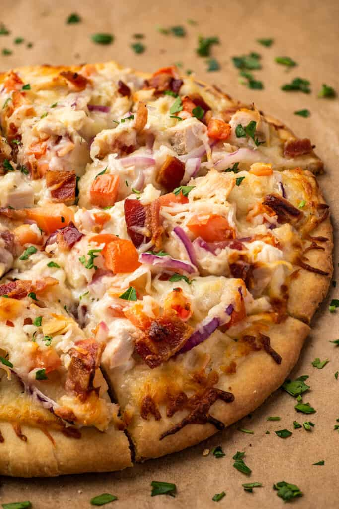 Bacon chicken ranch pizza on parchment paper.