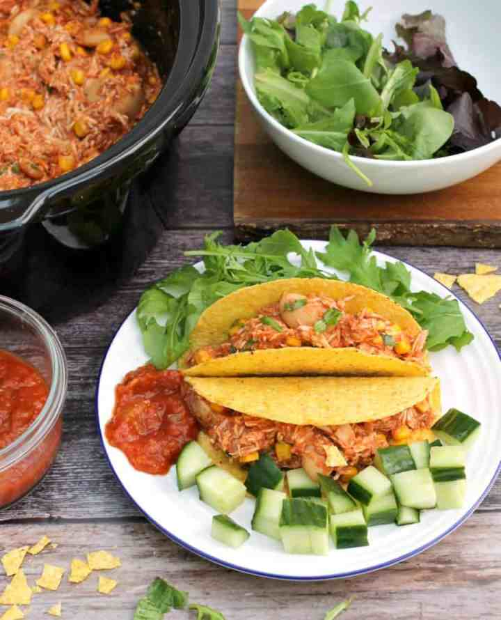 View of a plate with corn tacos filled with shredded chicken, with salad, and other plates around it with salsa and salad.